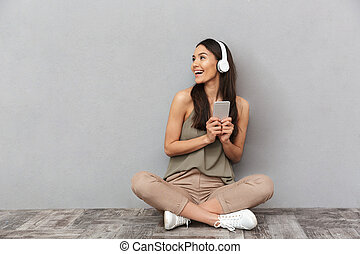 Portrait of a happy asian woman sitting on a floor