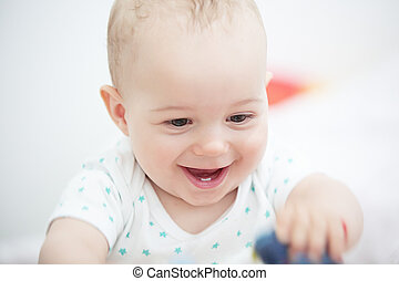 Portrait of a happy baby boy playing on floor in children's room