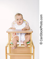 portrait of a happy baby in the highchair on a white background