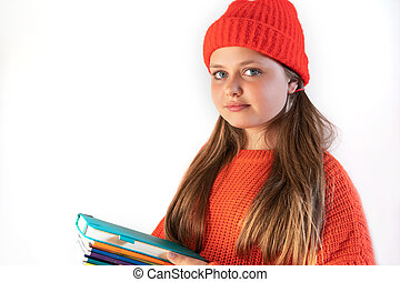 Portrait of a happy beautiful girl in winter red hat with school books