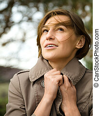 Portrait of a happy beautiful woman in autumn park