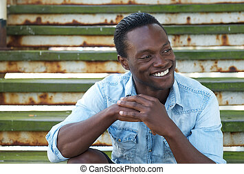 Portrait of a happy black man laughing outdoors