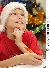boy in santa hat writing