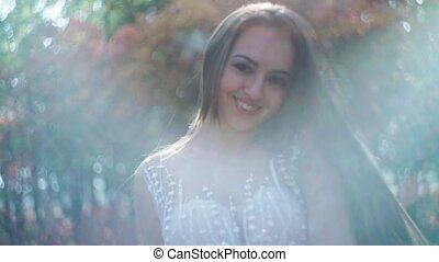 Portrait of a happy bride in white dress in the Park,...