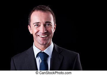Portrait of a happy  business man isolated on black background. Studio shot.
