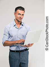 Portrait of a happy businessman using laptop