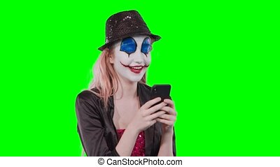 halloween clown make-up using mobile phone - Portrait of a...
