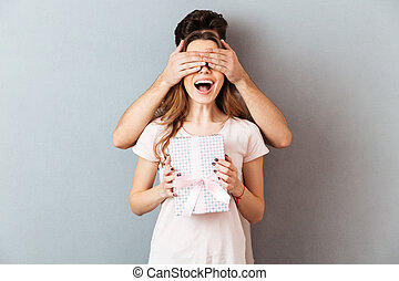 Portrait of a happy cheery girl holding present box