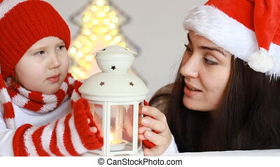 Portrait of a happy child and his mother in Santa Claus...
