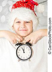 Portrait of a happy christmas child in santa hat keeps alarm clo