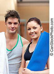 portrait of a happy couple after fitness exercices smiling to the camera in a fitness centre