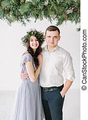 Portrait of a happy couple laughing at camera. Bridesmaid in pine wreath and groomsmen portrait. Funny wedding moment.