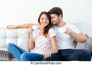 Portrait of a happy couple on the couch drinking coffee