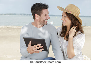 portrait of a happy couple using tablet near the sea
