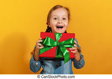 Portrait of a happy cute little girl in a denim shirt on a yellow background. The child holds a box with a gift in his hand