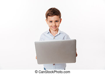 Portrait of a happy cute little kid holding laptop computer...