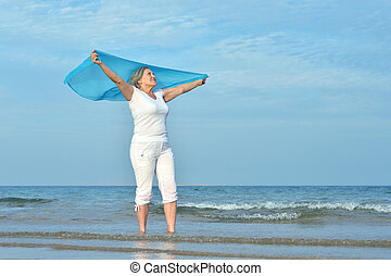 Portrait of a happy elderly woman on beach