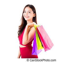 portrait of a happy excited asian woman in red dress standing and holding colorful shopping bags with happy isolated on a white background.