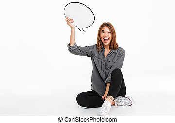 Portrait of a happy excited girl holding empty speech bubble...
