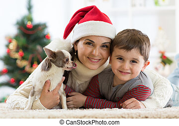 Portrait of a happy family and the dog spending together Christmas time at home near the x-mas tree
