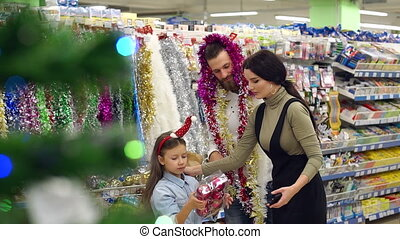 Portrait of a happy family in the supermarket before christmas.
