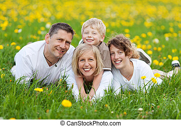 happy family lying on flower meadow