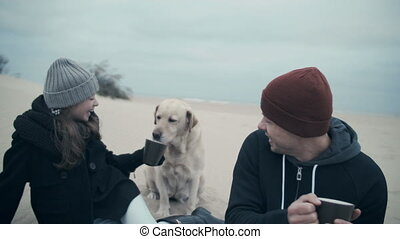 Portrait of a happy family on the beach. Have a picnic on the sea with a dog.