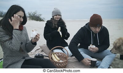 Portrait of a happy family on the beach. Have a picnic on...