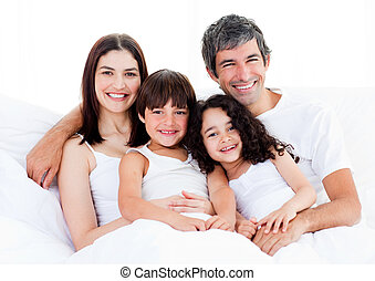Portrait of a happy family sitting on a bed
