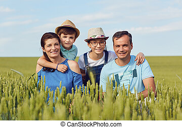 Portrait of a happy family sitting on nature in the grass.