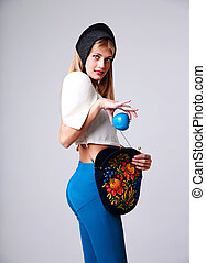 Portrait of a happy fashion woman holding blue apple over gray background