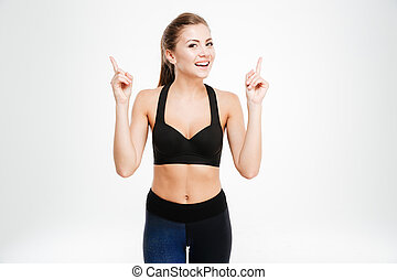 Portrait of a happy fitness woman pointing two fingers up ...