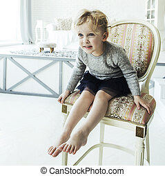 portrait of a happy five year old girl sitting on a chair in the spacious living room