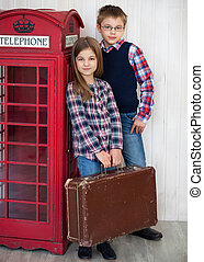 Portrait of a happy girl and a smiling boy with suit case
