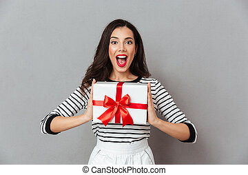 Portrait of a happy girl holding present box