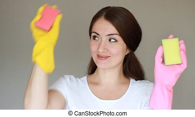 Portrait of a happy girl in rubber gloves looks at the...
