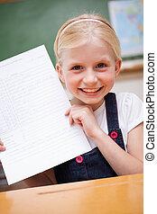 Portrait of a happy girl showing her school report