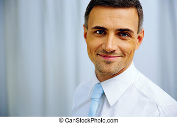 Portrait of a happy handsome businessman in white shirt