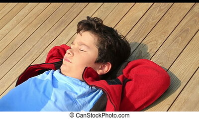 Portrait of a happy handsome young boy relaxing under the sun at the outdoor