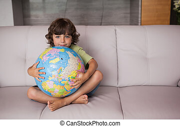 Portrait of a happy kid with globe in the living room