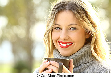 Portrait of a happy lady holding a cup of coffee