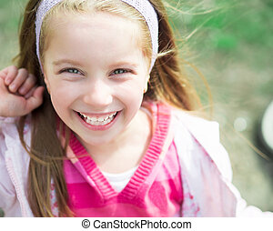 Close-up portrait of a cute liitle girl in park