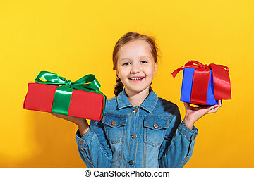Portrait of a happy little girl in a jeans shirt on a yellow background. The child holds boxes with gifts in his hands