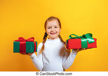 Portrait of a happy little girl in a white turtleneck on a yellow background. The child holds boxes with gifts in his hands