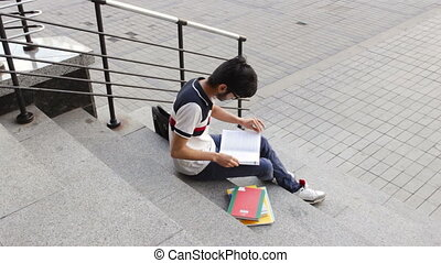 Portrait of a happy male asian student sitting on stairs and reading book in day
