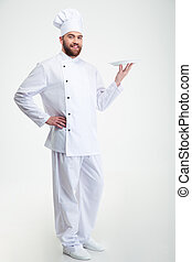 Portrait of a happy male chef cook standing with plate