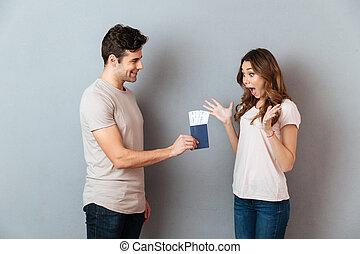 Portrait of a happy man giving his girlfriend passport