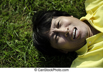 portrait of a happy man laying on grass