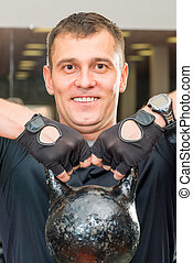 portrait of a happy man lift heavy dumbbell