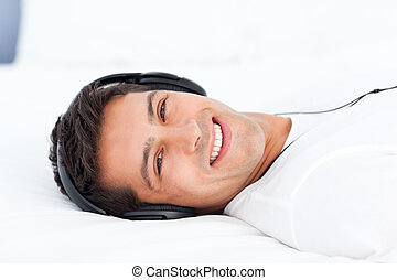 Portrait of a happy man listening music lying on his bed